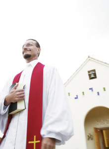 Priest Standing in Front of Church